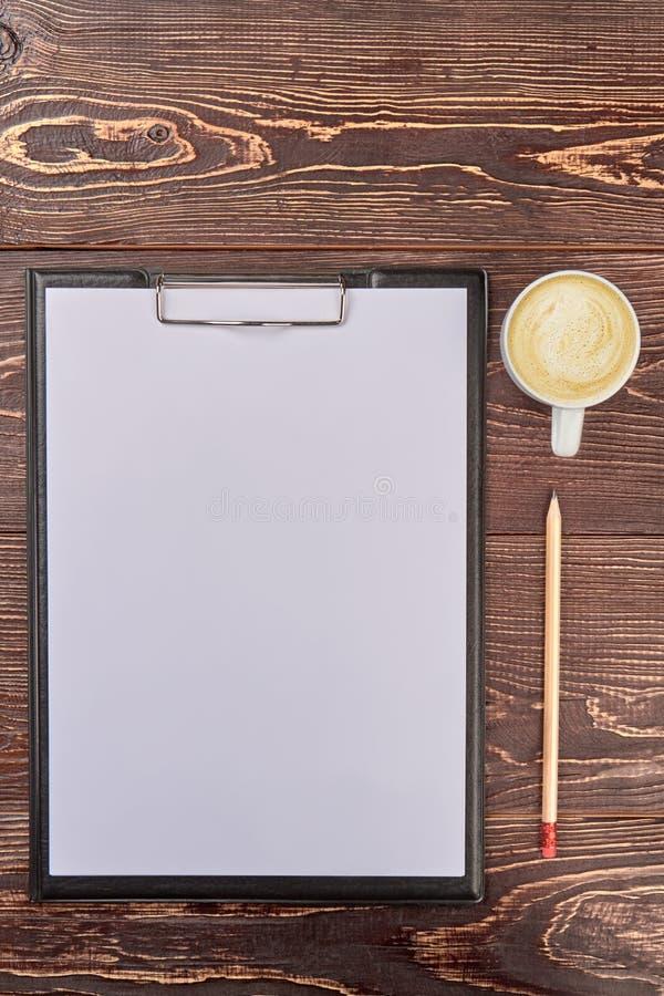 Klembord met blanco pagina en kop van koffie op houten bureau stock afbeeldingen