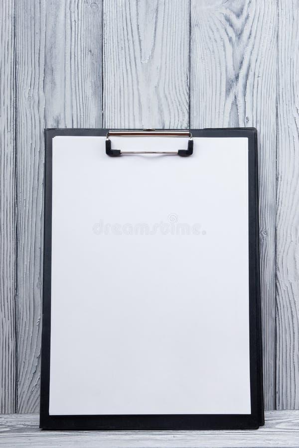 Klembord met leeg blad van document op houten achtergrond De ruimte van het exemplaar royalty-vrije stock afbeeldingen