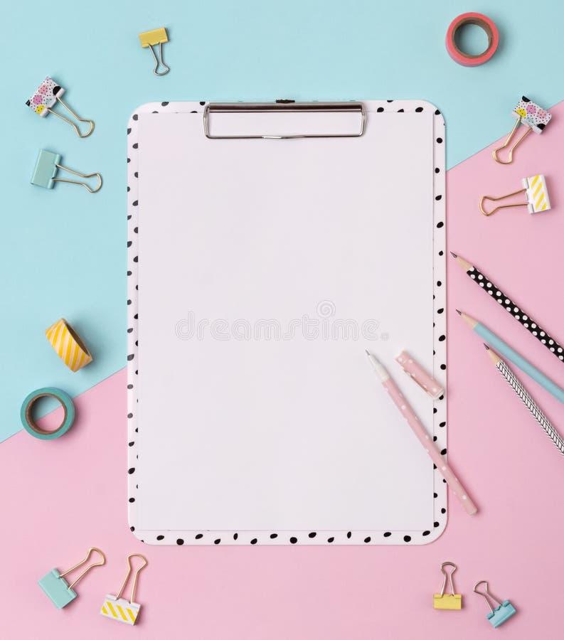 Klembord, pen, bindmiddel, potlood en buisband op een creatieve roze en blauwe achtergrond stock foto