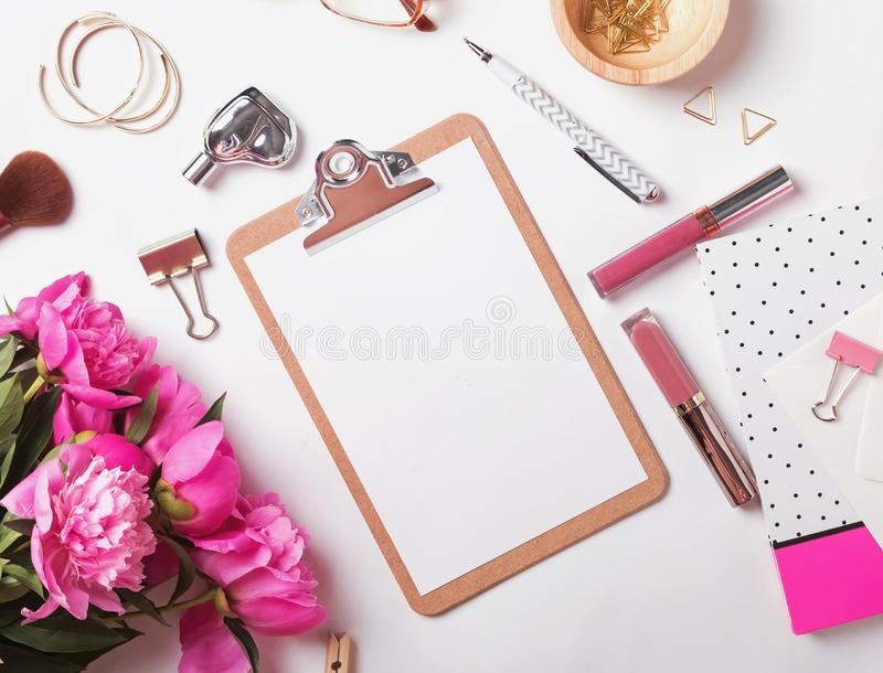 Klembordprototype op de vrouwelijke werkplaats met pioenen en stationair stock foto's