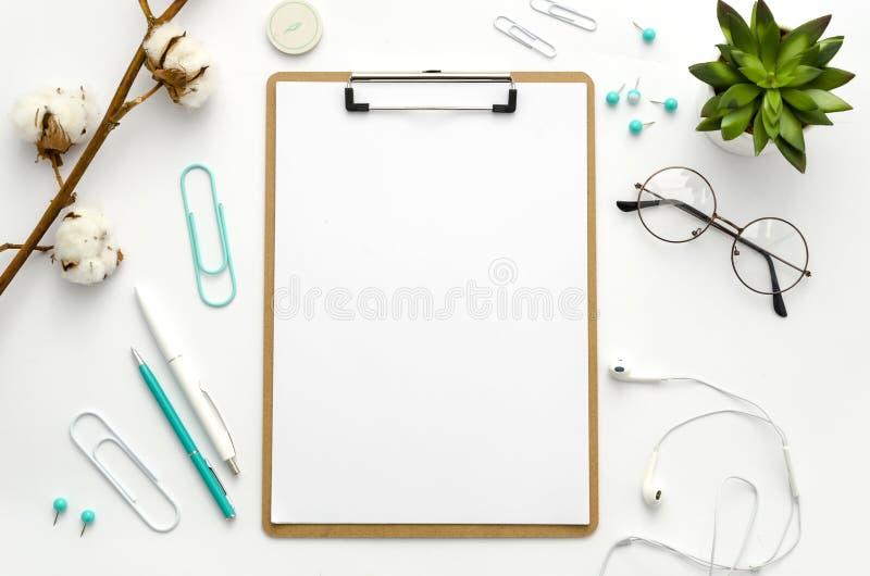 Klembordspot omhoog De de werkruimtevlakte van het huisbureau legt model met klembord, bloemen en blauwe toebehoren Vlak leg, bov stock fotografie