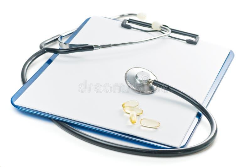 Klemmbrett mit dem Stethoskop getrennt auf einem Weiß lizenzfreie stockfotos