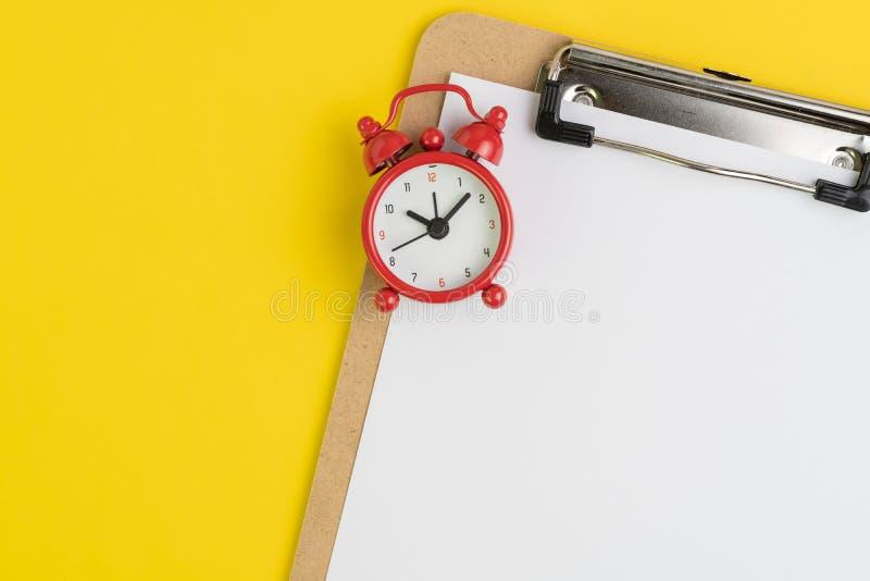 Klemmbrett mit leerem Weißbuch mit gelesenem Wecker auf festem gelbem Hintergrund mit Kopienraum für das Schreiben der Mitteilung lizenzfreies stockbild
