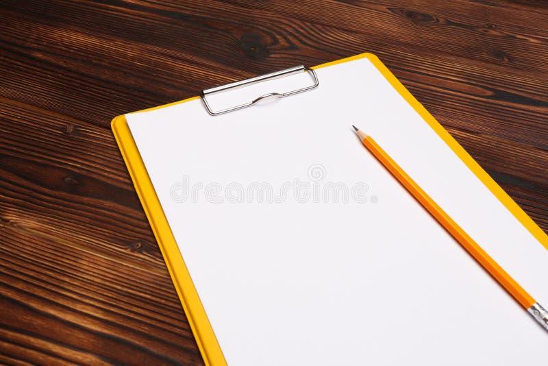 Klemmbrett mit weißem Blatt auf hölzernem Hintergrund Beschneidungspfad eingeschlossen stockfotografie