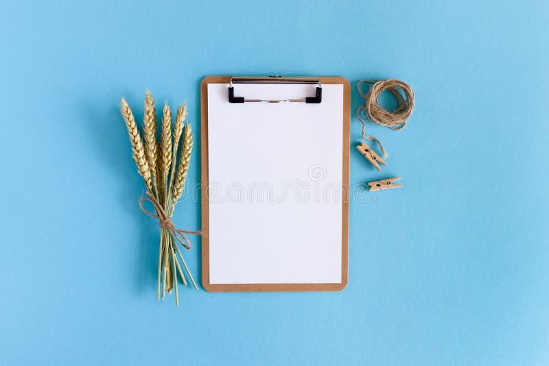 Klemmbrett mit weißem leerem Papier, Blumenstrauß von Weizenährchen, Schnurseil, hölzerne Wäscheklammern stockfotografie