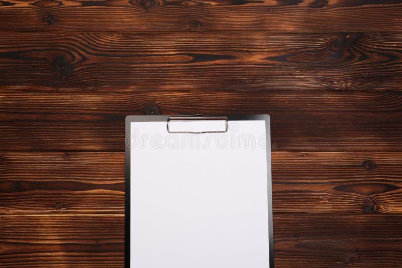 Klemmbrett mit wei?em Blatt auf h?lzernem Hintergrund Beschneidungspfad eingeschlossen lizenzfreie stockfotografie