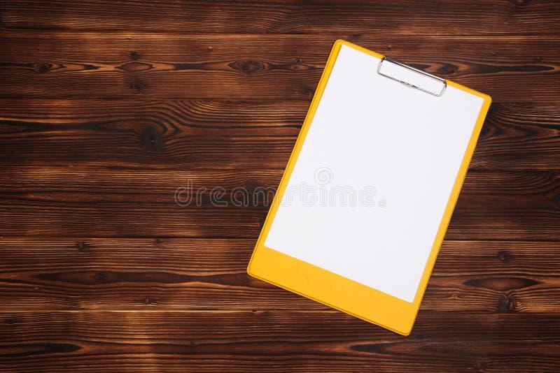 Klemmbrett mit wei?em Blatt auf h?lzernem Hintergrund Beschneidungspfad eingeschlossen lizenzfreie stockfotos