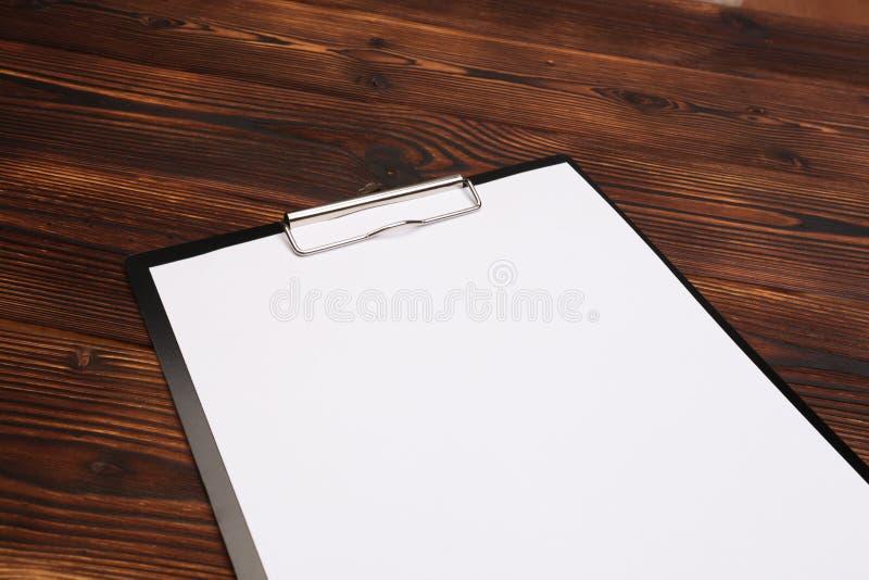 Klemmbrett mit wei?em Blatt auf h?lzernem Hintergrund Beschneidungspfad eingeschlossen stockfotos