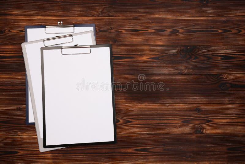 Klemmbrett mit wei?em Blatt auf h?lzernem Hintergrund Beschneidungspfad eingeschlossen stockfoto