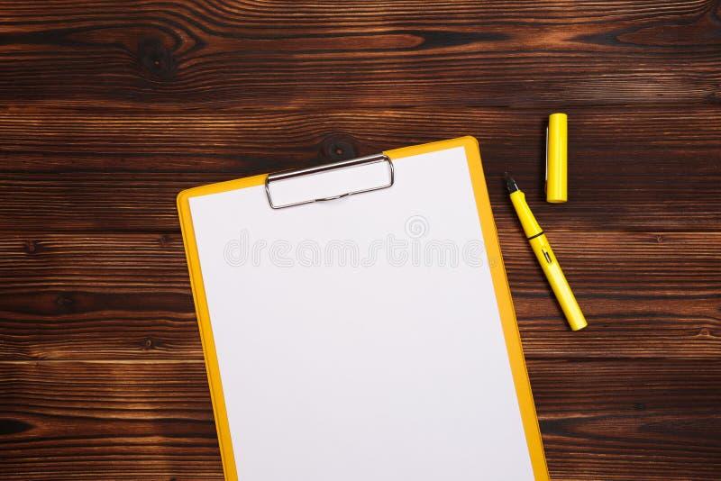 Klemmbrett mit wei?em Blatt auf h?lzernem Hintergrund Beschneidungspfad eingeschlossen lizenzfreies stockbild