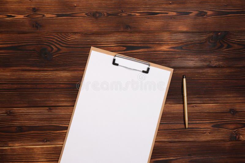 Klemmbrett mit wei?em Blatt auf h?lzernem Hintergrund Beschneidungspfad eingeschlossen stockfotografie