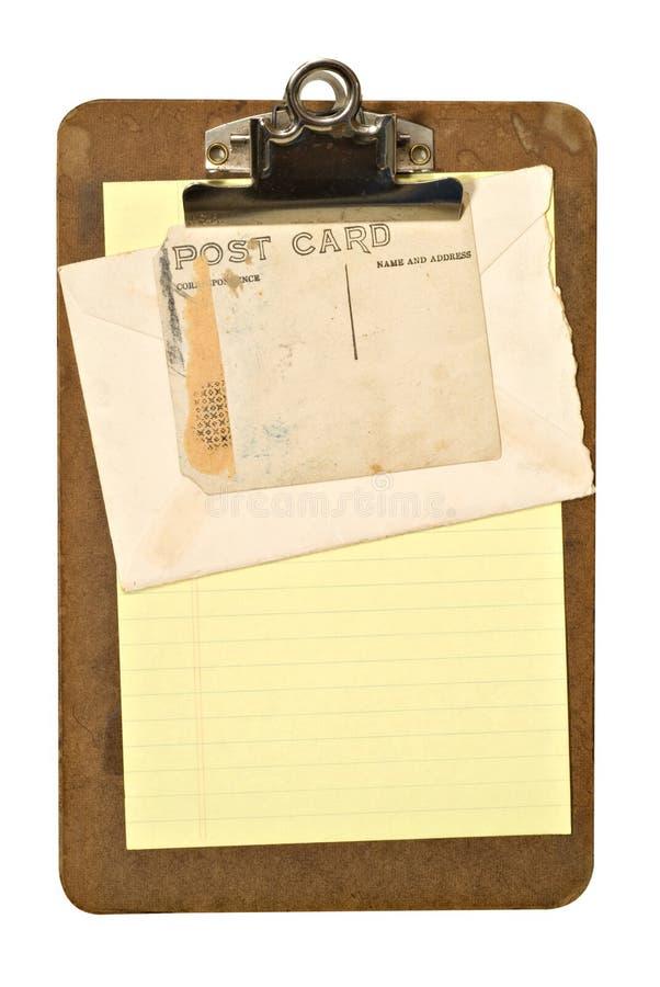 Klemmbrett, Umschlag und Postkarte lizenzfreie stockfotos
