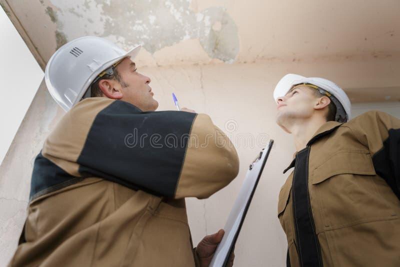 Klempner, der Deckenleck betrachtet stockbild