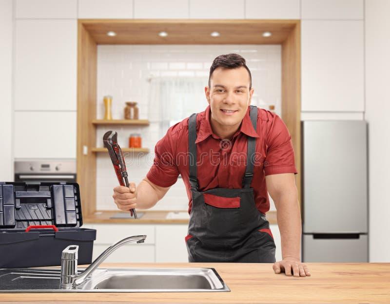 Klempner mit einem Rohrschlüssel und eine Werkzeugkastenstellung hinter einer Wanne in einer Küche stockfotografie