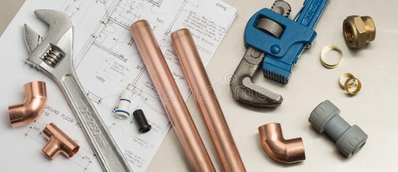 Klempner-Werkzeug-und Klempnerarbeit-Material-Fahne auf Haus-Plänen stockfotografie