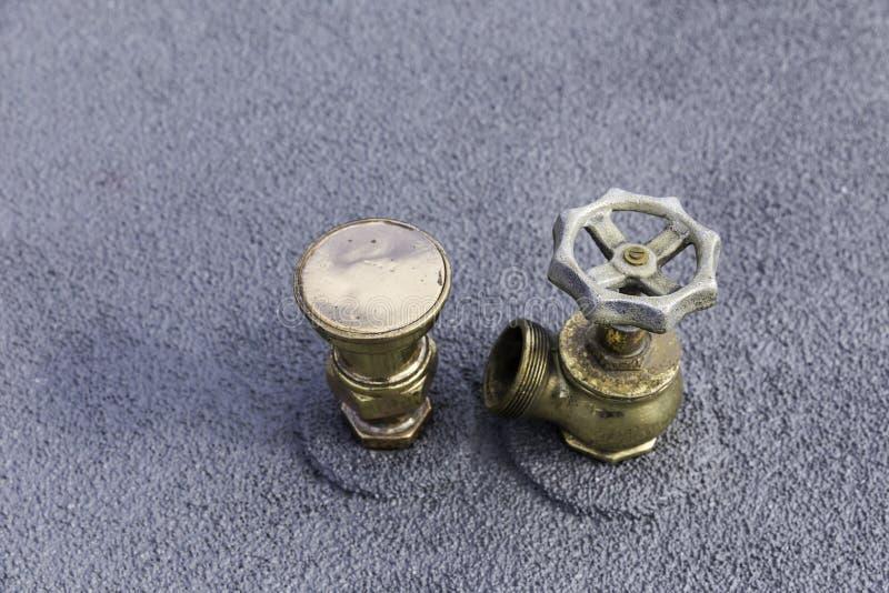 Klempnerarbeitkupferrohr mit einem einzelnen Ventil auf einer grauen Metalloberfläche stockfotos