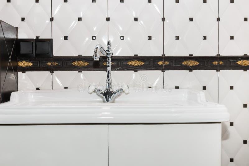 Klepnięcie i washbasin z pięknymi płytkami na ścianie w łazienki wnętrzu w górę fotografia royalty free