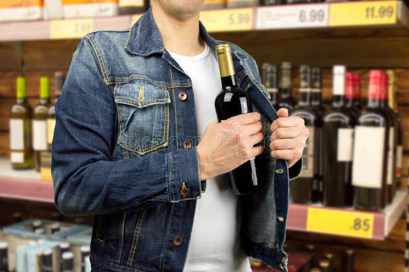 Kleptomania. Man in a supermarket stealing a bottle of champagne stock photography