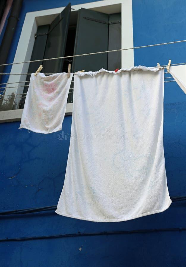 kleren die uit van een blauw-gekleurd huis hangen uit te drogen stock afbeelding