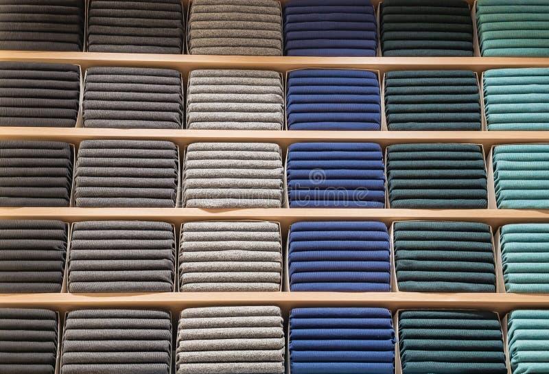 Kleren in opslag worden getoond die Exemplaarspase voor tekst Worden de partij warme sweaters van verschillende kleur keurig gest royalty-vrije stock foto