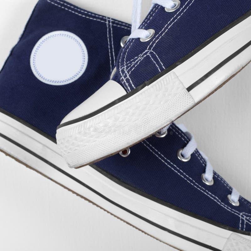 Kleren, schoenen en toebehoren - het paar van het Close-upfragment gumshoes hangt neer op kant royalty-vrije stock foto