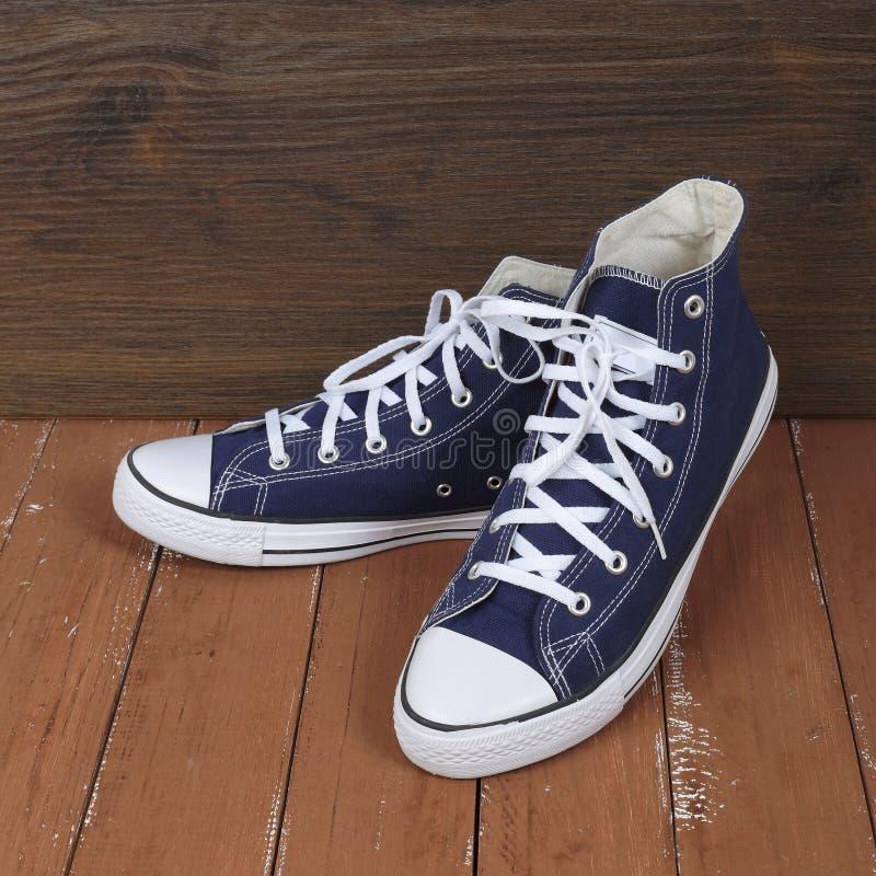 Kleren, schoenen en toebehoren - houten achtergrond van paar de blauwe gumshoes stock foto