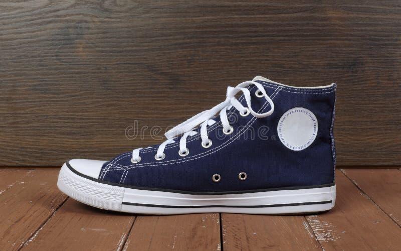 Kleren, schoenen en toebehoren - zijaanzicht ??n blauwe gumshoes houten achtergrond royalty-vrije stock afbeeldingen