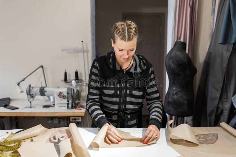 Kleren van een vouwden de jonge meisjesontwerper document voor een patroon Het maken van kleren aan orde, het concept van de mani royalty-vrije stock afbeelding
