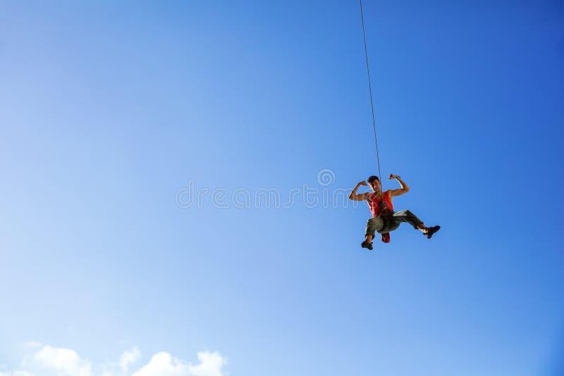 Kletterer, der auf Seil schwingt und Muskeln biegt lizenzfreies stockfoto