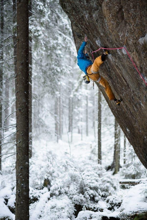 Kletterer, der im schönen felsigen Bereich klettert Winterabenteuer-Sportkonzept Extreme Tätigkeit lizenzfreie stockfotografie