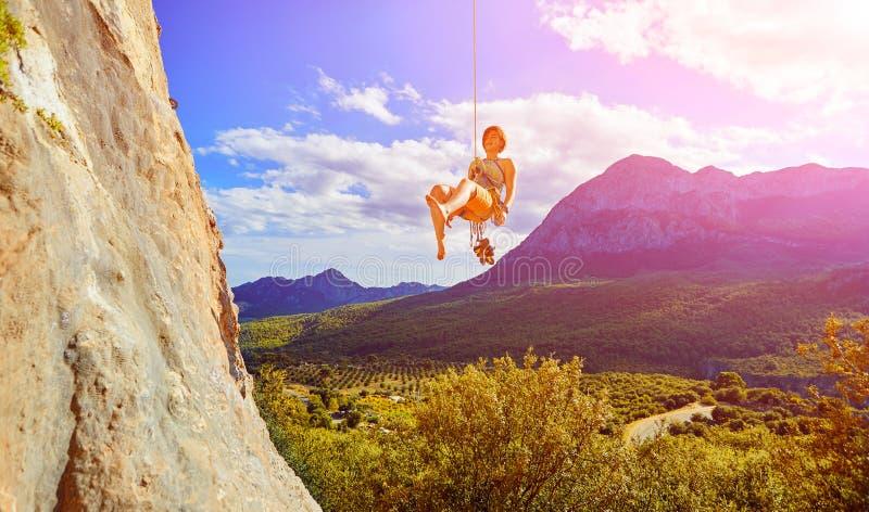 Kletterer, der oben eine Klippe klettert stockfotografie