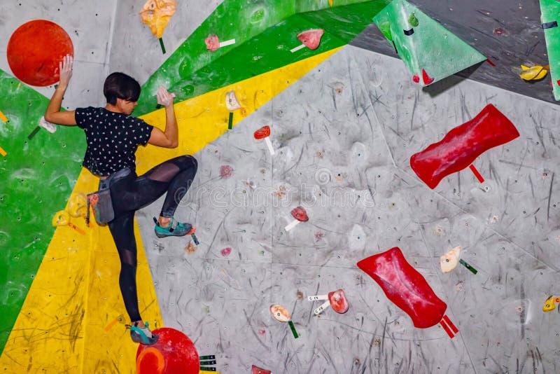 Klettererfrau, die an einem bouldering Kletterwand, nach innen auf farbigen Haken hängt lizenzfreies stockfoto