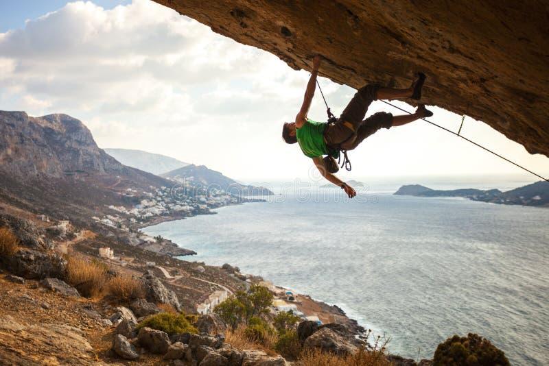 Kletternder überhängender Felsen des männlichen Bergsteigers stockfotografie