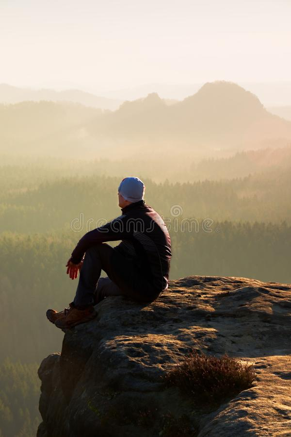 Kletternder erwachsener Mann an der Spitze des Felsens mit schöner Vogelperspektive des tiefen nebelhaften Tales brüllen stockfoto