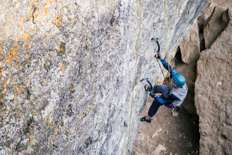Kletternder Mann auf einem Felsen stockbilder
