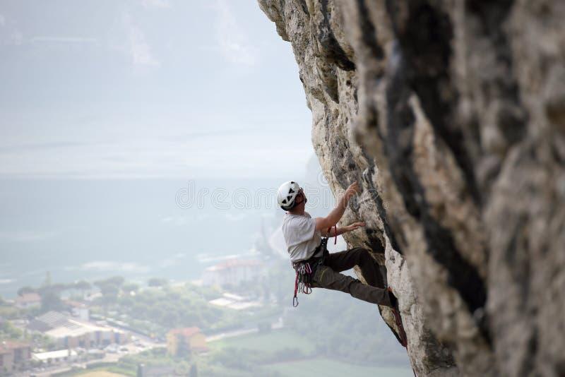 Kletternder Mann auf einer Steinwand stockbild