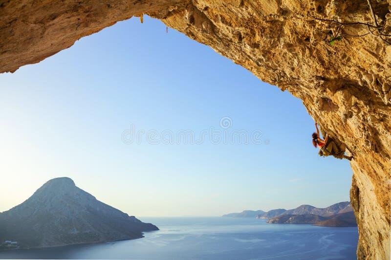 Kletternder schwieriger Weg der jungen Frau in der Höhle stockbild