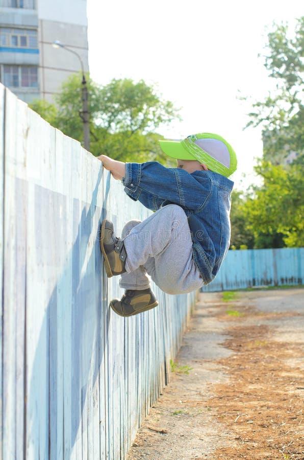 Kletternder Zaun des kleinen Jungen draußen lizenzfreies stockbild