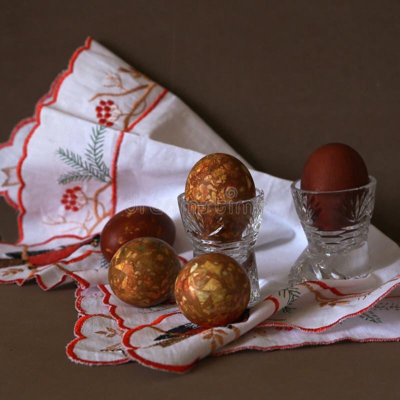 Kleurde een uienschil van ei in kristalglazen door een lichte vakantie van Pasen op het geborduurde witte servet royalty-vrije stock afbeeldingen