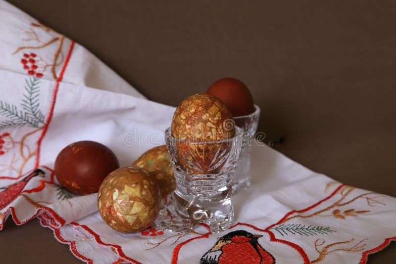 Kleurde een uienschil van ei in kristalglazen door een lichte vakantie van Pasen op het geborduurde witte servet stock fotografie