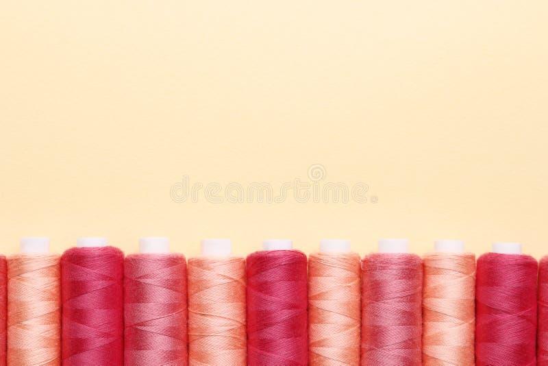 Kleuren naaiende draden op document achtergrond stock afbeelding