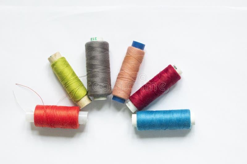 Kleuren naaiende draden op witte achtergrond stock afbeeldingen