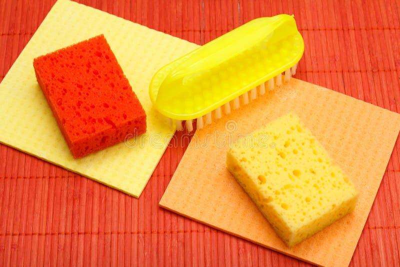 Kleuren synthetische sponsen, microfiber servetten en borstel voor het schoonmaken op bamboe stock foto