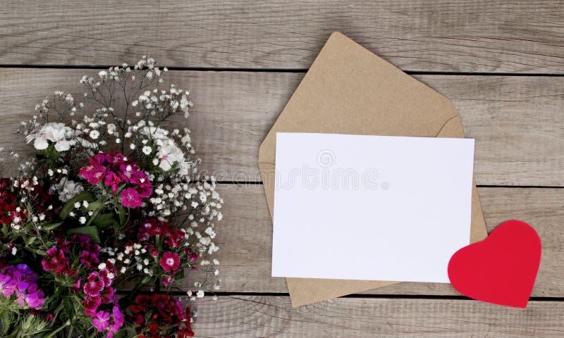 Kleurenbloemen, hartvorm en envelop op houten achtergrond De dag van de valentijnskaart `s stock afbeelding