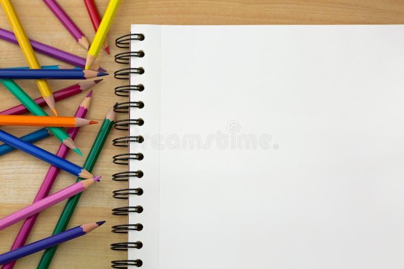 Kleurende kleurpotloden naast het boek van de schetstekening op houten B stock foto's