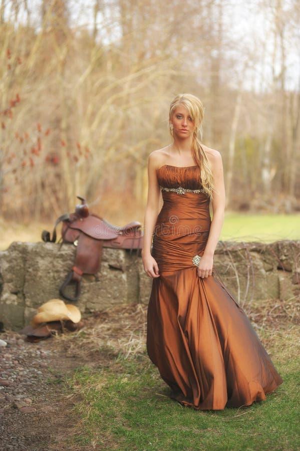Kleurenfoto van een mooie jonge blondevrouw die met grote blauwe ogen camera onderzoeken royalty-vrije stock afbeeldingen
