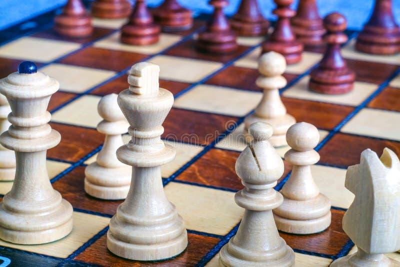 Kleurenfoto van schaakraad en schaakstukken, houten schaakstukken op het schaakbord De witte Koningin en de Koning in de voorgron royalty-vrije stock foto