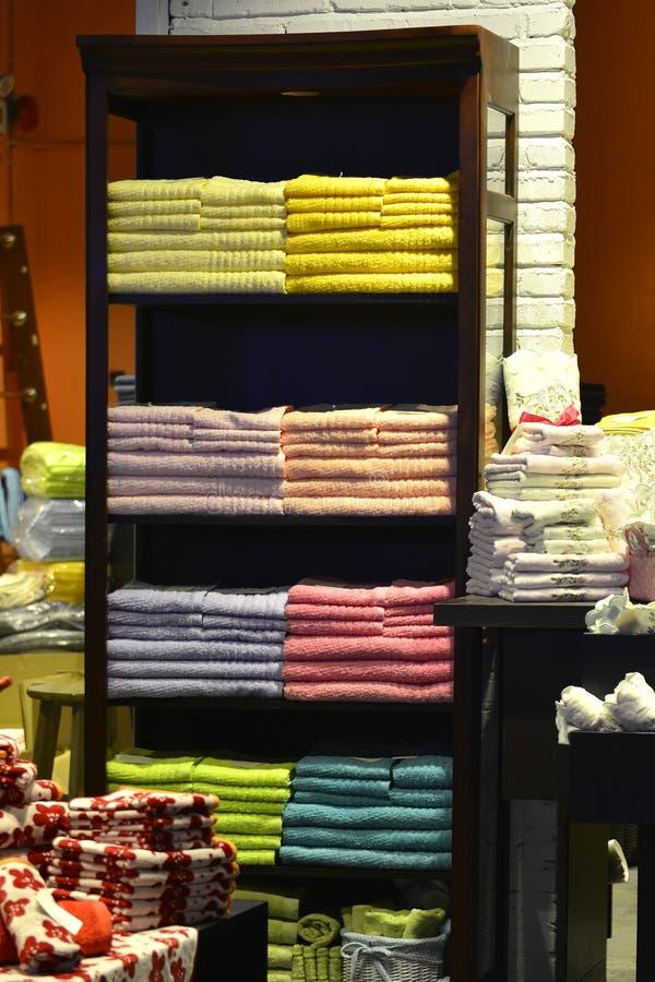 Kleurenhanddoek op de plank in manierwinkel die keurig wordt gestapeld stock afbeeldingen