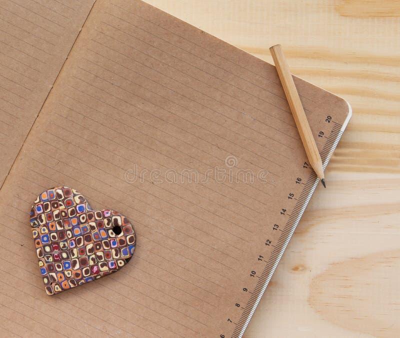 Kleurenhart die op het notitieboekje en de pan liggen royalty-vrije stock foto
