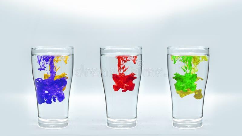 Kleureninkt binnen een glas water stock foto